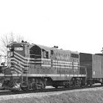 The week-end of April 26, 1958 saw the moving of the highest and widest load moved by rail at that time. It was a 91 ton atomic reactor vessel for a power plant near Detroit, Michigan. Built in Chattanooga, it was delivered by barge to the B&O in Cincinnati, then to the NKP at Rushville, to the C&O at Muncie, to the NKP at Marion, across town to the NYC, then back to the NKP Clover Leaf. There must have a weight or clearance issue to cause the Marion shuffle, but once it was back on the NKP it was interchanged to the IMC division at Kokomo and then went north to Belfast to be interchanged with the C&O for its trip to the Detroit area. The picture is near Belfast, Indiana. Photograph is from the Bob Albert collection.