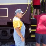 Member Fred Boyer assists passengers boarding the train.