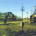 In the spring of 1964, the Nickel Plate Road is still providing high speed service for its customers, as shown by the blurred RS36 on the eastbound extra. GP30 #900 is making a set out and pick up from the Argos, Indiana yard. The trainman waves a friendly greeting to the eastbound as he inspects the train on the south side. In October 1964 the NKP will be merged into the N&W and scene like this will cease to exist. Photo by Bob Albert.