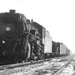 Erie 2-8-2 3057 is westbound at Rochester, Indiana on December 27, 1947. Judging by the short train length, this is probably a local freight. Behind the caboose you can see the tower that protected the Nickel Plate crossing, one can see the water column near the center of the picture and the top of the water tank above the depot, the concrete tank base is still there. Photo is courtesy of M. D. McCarter Photographs; please check our links page for his catalog.
