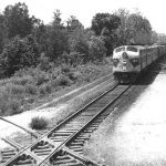 "Erie E8a 819 appears to have the eastbound ""Lake Cities"" well in hand in June 1965 at Newton Tower east of Laketon, Indiana. The 819 is about to cross the Pennsy's Butler branch, which ran northeast from Logansport. Notice the signal rods on the left side of the track; at one time the Erie was double tracked through here. That's Bern Kelker's 1956 Plymouth V8 behind the GMC pick-up. Photo by Bernard Kelker."