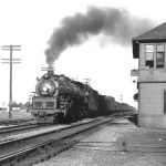 B&O engine #5584 is crossing the C&O's Pere Marquette District at Wellsboro, Indiana. The Grand Trunk Western crossing is about the fifth car back from the tender and the depot is barely visible behind the tower. The date is unknown, but must have been the early to mid 1950s, note the B&O semaphore still in use. The tower was razed in the late 1950s, the depot was destroyed by a GTW train wreck on November 21, 1985 and the C&O diamond was removed in 1998. Photo is courtesy of Harry Zillmer.