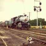 It is July 4, 1973 and Southern Railway 4501 leaving Argos, Indiana after stopping for a drink from a city fire hydrant. The train is eastbound, just east of the IMC District crossing. Do you suppose the girl in the picture remembers waving to the engineer? The N&W is getting ready to put down welded rail on the former Nickel Plate. The engine track on the left is now gone and the dwarf and signals has been replaced with a signal bridge. Photo by Bob Albert.