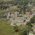"This is another great aerial view of Mentone, Indiana from about 1957. Some of the structures from the previous view are still there, but the Winona Railway is gone. The white building on the right with the red stripe is the Winona's substation and depot. It is still standing as a mini-mart. Directly across US25 is the giant egg, Mentone was known as 'the egg basket of the Midwest"". The former Winona right of way can be seen curving behind the hardware. There was a connection built to the Nickel Plate to service the elevator. Photo provided by the Bell Aircraft Museum at Mentone."